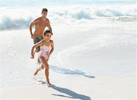 Father and daughter running in surf at beach Stock Photo - Premium Royalty-Free, Code: 6113-07147785
