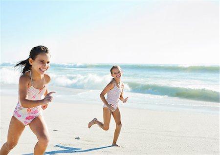 Girls running on beach Stock Photo - Premium Royalty-Free, Code: 6113-07147793