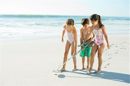 Children using metal detector on beach Stock Photo - Premium Royalty-Free, Code: 6113-07147791