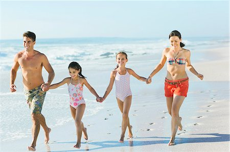 Family holding hands and running on beach Stock Photo - Premium Royalty-Free, Code: 6113-07147795