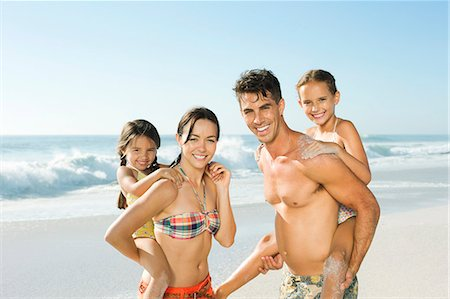 Parents carrying daughters piggyback on beach Stock Photo - Premium Royalty-Free, Code: 6113-07147719