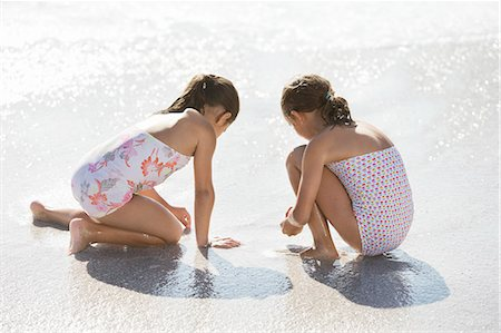 Girls playing together in surf on beach Stock Photo - Premium Royalty-Free, Code: 6113-07147727