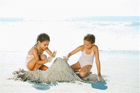 Girls building sandcastle on beach Stock Photo - Premium Royalty-Free, Code: 6113-07147733