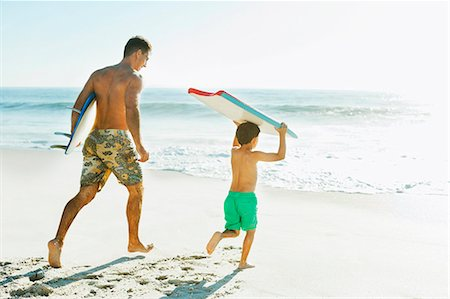families playing on the beach - Father and son carrying surfboard and bodyboard on beach Stock Photo - Premium Royalty-Free, Code: 6113-07147803