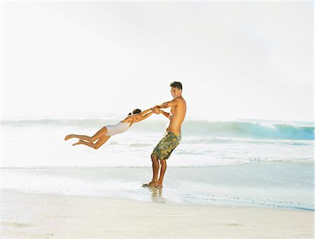 Father swinging daughter on beach Stock Photo - Premium Royalty-Free, Code: 6113-07147804
