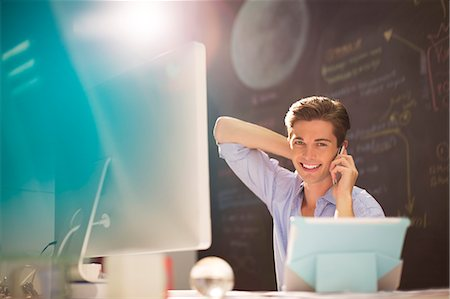 Businessman talking on cell phone at desk in office Stock Photo - Premium Royalty-Free, Code: 6113-07147946