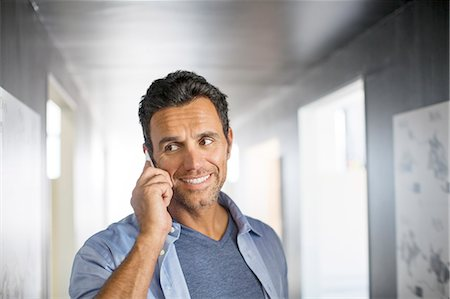 Businessman talking on cell phone in corridor Stock Photo - Premium Royalty-Free, Code: 6113-07147960