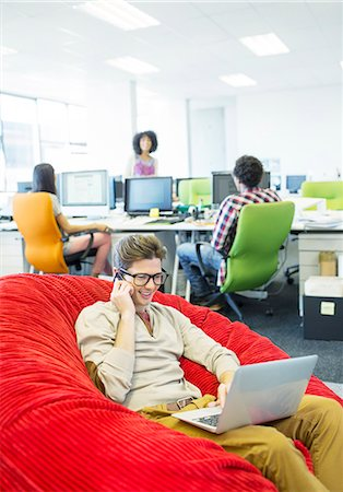 Businessman working in beanbag chair in office Stock Photo - Premium Royalty-Free, Code: 6113-07147972