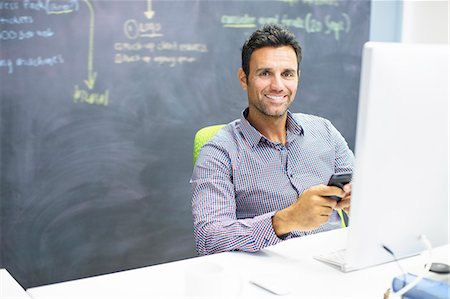 Businessman using cell phone at desk in office Foto de stock - Sin royalties Premium, Código: 6113-07147914