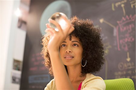 Businesswoman examining crystal ball in office Stock Photo - Premium Royalty-Free, Code: 6113-07147933