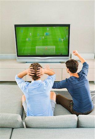 soccer fan - Men watching soccer game on sofa Stock Photo - Premium Royalty-Free, Code: 6113-07148003