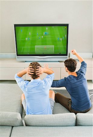 Men watching soccer game on sofa Stock Photo - Premium Royalty-Free, Code: 6113-07148003