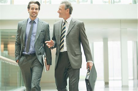 Businessmen talking in office lobby Stock Photo - Premium Royalty-Free, Code: 6113-07158952