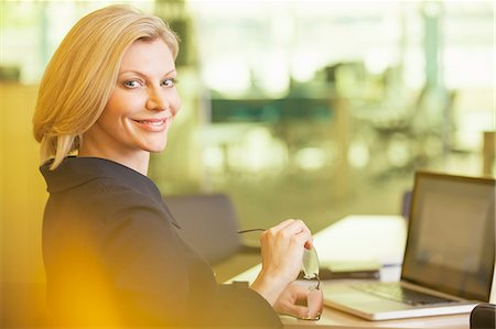 Businesswoman smiling at desk in office Stock Photo - Premium Royalty-Free, Code: 6113-07158959