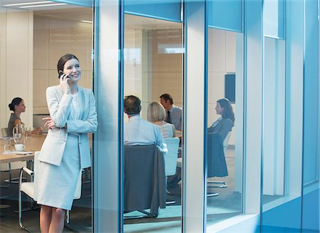 Businesswoman talking on cell phone in meeting Stock Photo - Premium Royalty-Free, Code: 6113-07158971