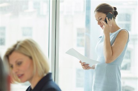 Businesswoman talking on cell phone in office Stock Photo - Premium Royalty-Free, Code: 6113-07158909