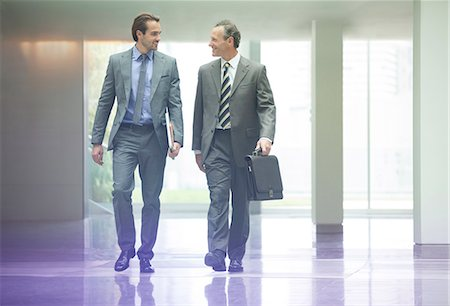 Businessmen talking in office lobby Stock Photo - Premium Royalty-Free, Code: 6113-07159009