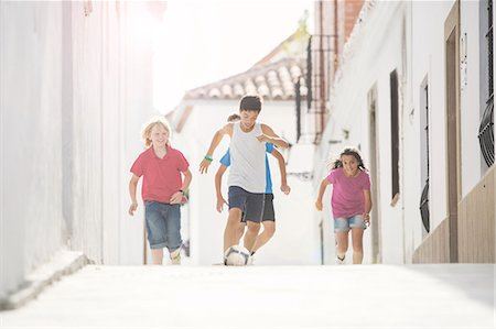 female playing soccer - Children playing soccer in alley Stock Photo - Premium Royalty-Free, Code: 6113-07159143