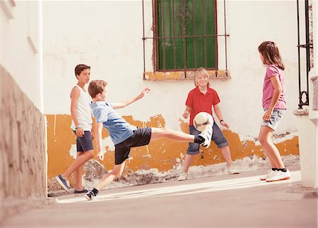 preteen boys playing - Children playing with soccer ball in alley Stock Photo - Premium Royalty-Free, Code: 6113-07159141
