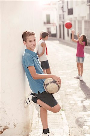 preteen boys playing - Boy holding soccer ball in alley Stock Photo - Premium Royalty-Free, Code: 6113-07159145