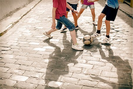 female playing soccer - Children playing with soccer ball on cobblestone street Stock Photo - Premium Royalty-Free, Code: 6113-07159149