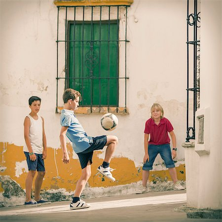 preteen boys playing - Children playing with soccer ball in alley Stock Photo - Premium Royalty-Free, Code: 6113-07159150