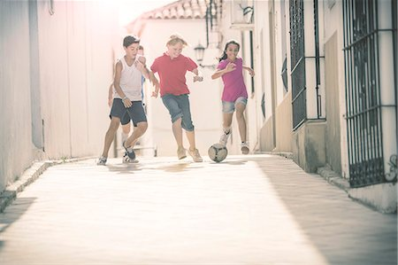 female playing soccer - Children playing with soccer ball in alley Stock Photo - Premium Royalty-Free, Code: 6113-07159152
