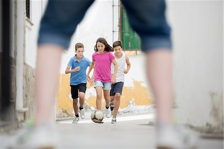 female playing soccer - Children playing with soccer ball in alley Stock Photo - Premium Royalty-Free, Code: 6113-07159156