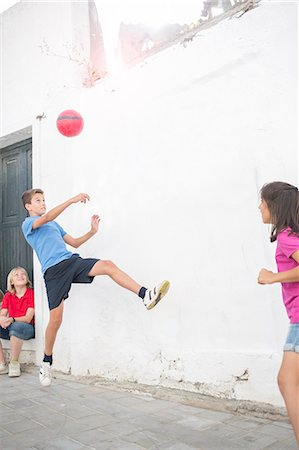female playing soccer - Children playing with soccer ball in alley Stock Photo - Premium Royalty-Free, Code: 6113-07159159