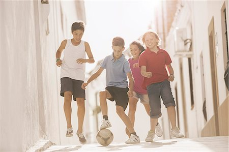 female playing soccer - Children playing with soccer ball in alley Stock Photo - Premium Royalty-Free, Code: 6113-07159162