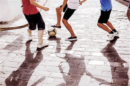 preteen boys playing - Children playing with soccer ball in alley Stock Photo - Premium Royalty-Free, Code: 6113-07159167