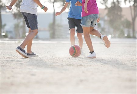 sports - Children playing with soccer ball in sand Stock Photo - Premium Royalty-Free, Code: 6113-07159165