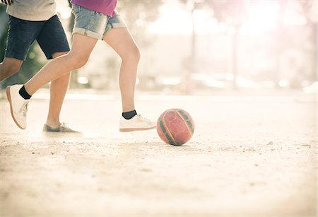 female playing soccer - Children playing with soccer ball in sand Stock Photo - Premium Royalty-Free, Code: 6113-07159169