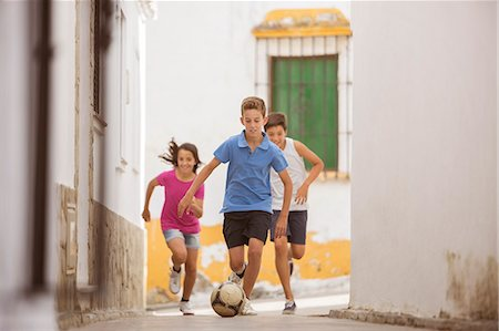preteen boys playing - Children playing with soccer ball in alley Stock Photo - Premium Royalty-Free, Code: 6113-07159172