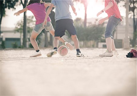 female playing soccer - Children playing with soccer ball in sand Stock Photo - Premium Royalty-Free, Code: 6113-07159175