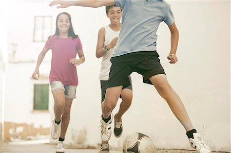 female playing soccer - Children playing with soccer ball in alley Stock Photo - Premium Royalty-Free, Code: 6113-07159179