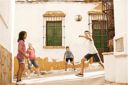preteen boys playing - Children playing with soccer ball in alley Stock Photo - Premium Royalty-Free, Code: 6113-07159183