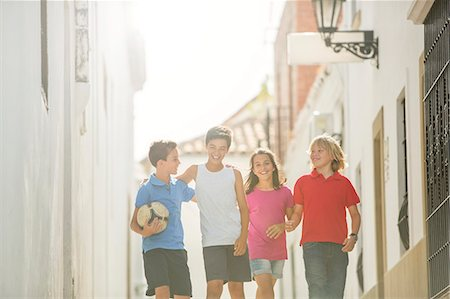 Children with soccer ball walking in alley Stock Photo - Premium Royalty-Free, Code: 6113-07159180
