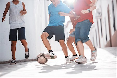 preteen boys playing - Children playing with soccer ball in alley Stock Photo - Premium Royalty-Free, Code: 6113-07159182