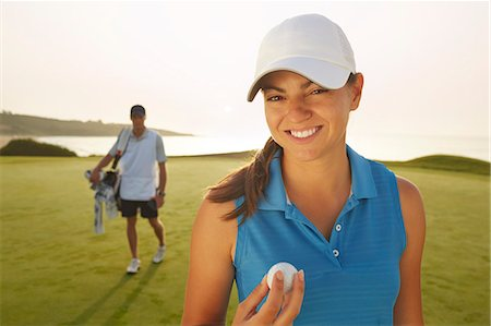 Woman holding golf ball on course Stock Photo - Premium Royalty-Free, Code: 6113-07159193