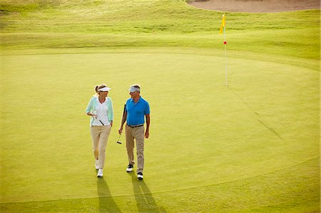 Senior couple walking on golf course Stock Photo - Premium Royalty-Free, Code: 6113-07159190