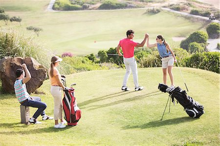 Friends playing golf on course Stock Photo - Premium Royalty-Free, Code: 6113-07159196