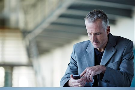 Businessman using cell phone Stock Photo - Premium Royalty-Free, Code: 6113-07159102