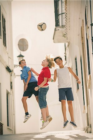 preteen boys playing - Children playing with soccer ball in alley Stock Photo - Premium Royalty-Free, Code: 6113-07159137