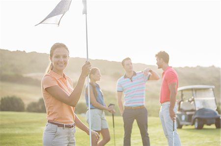 Smiling friends on golf course Stock Photo - Premium Royalty-Free, Code: 6113-07159273