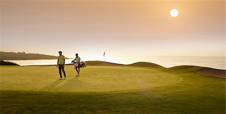 Golfer and caddy walking on golf course Stock Photo - Premium Royalty-Free, Code: 6113-07159272