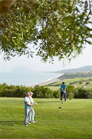 Older friends playing golf on course Stock Photo - Premium Royalty-Free, Code: 6113-07159286