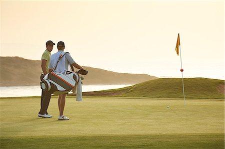 Men on golf course overlooking ocean Stock Photo - Premium Royalty-Free, Code: 6113-07159200