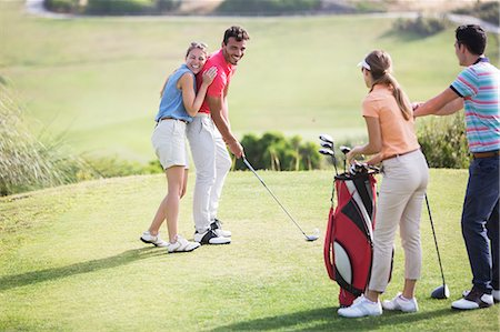 Friends laughing on golf course Stock Photo - Premium Royalty-Free, Code: 6113-07159202