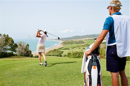 Caddy watching woman tee off on golf course overlooking ocean Stock Photo - Premium Royalty-Free, Code: 6113-07159207